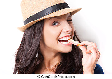 Sweet candy. Young beautiful woman in funky hat eating candy...