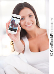 Making selfie Beautiful young smiling woman sitting in bed...