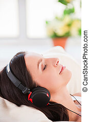 Listening to the music in bed. Side view of cheerful young woman in headphones listening to MP3 player and keeping eyes closed