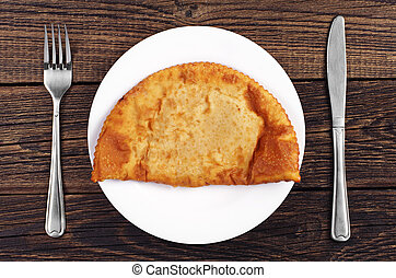 Large pasties in a plate on wooden background. Top view