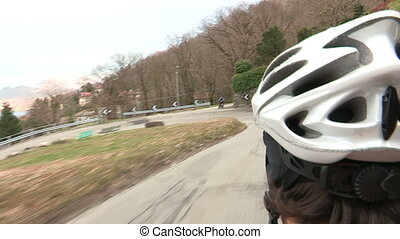Cyclist going downhill. Camera behind his helmet