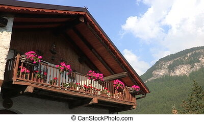 Typical mountain house in summer in Italy with pink flowers