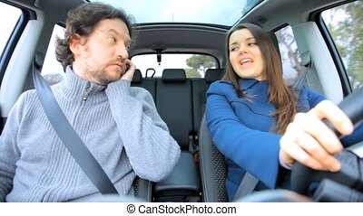 Couple in car talking on the phone with parents about...