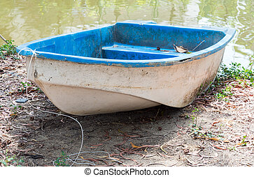 Old plastic rowboat near the river of reservoir.