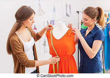 Working on new collection together. Two beautiful female designers measuring dress on the mannequin