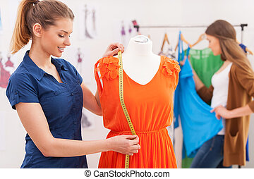 Designer measuring dress. Beautiful female fashion designer measuring dress on the mannequin while her colleague standing on background
