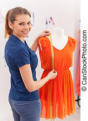Confident fashion designer. Beautiful female fashion designer measuring dress on the mannequin and looking over shoulder