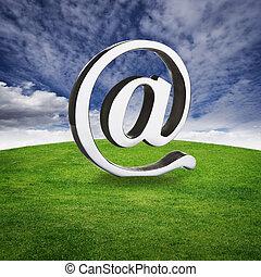 At symbol on a grassy hill