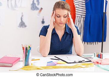 Trying to reach deadline. Depressed female fashion designer holding head in hands while sitting at her working place