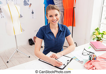 Confident fashion designer. Top view of attractive female fashion designer sketching and looking at camera while sitting at her working place