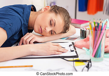 Tired fashion designer. Tired fashion designer sleeping at her working place