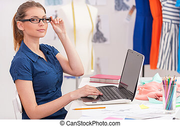 Confident fashion designer at work. Side view of attractive female fashion designer working on laptop and smiling while sitting at her working place