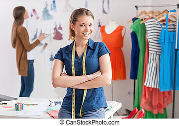 Fashion designers at work. Beautiful young woman with measuring tape on shoulders looking at camera and smiling while her colleague standing on background