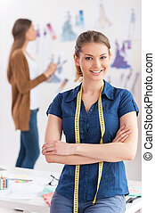 Confident fashion designer. Attractive young woman with measuring tape on shoulders looking at camera and smiling while her colleague standing on background