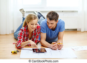 smiling couple looking at tablet pc at home - repair,...