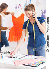 Busy working in design studio. Beautiful young female designer with measuring tape on shoulders talking on the mobile phone while her colleague standing on background