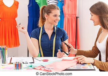 Working on new collection together. Two beautiful female designers talking and smiling while sitting at the working place