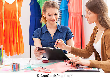 Working on new fashion look together. Two beautiful female designers discussing something while sitting at the working place
