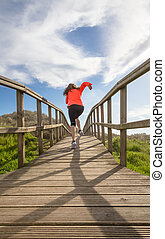 Back view of girl running in a wood boardwalk - Back view of...
