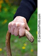 Wrinkled hands - Close up of wrinkled hands holding a cane
