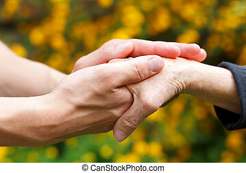 Giving help - Doctors hand holding a wrinkled elderly hand