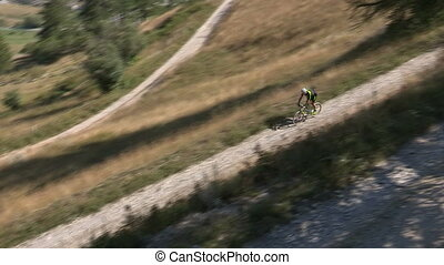 Cyclist going downhill on trail - Cyclist going downhill on...