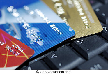 Credit cards laying on laptop keyboard close up photography.