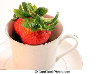 Red ripe strawberries sit inside a white china teacup atop a...