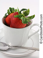Fresh red strawberries sit inside a white china teacup on a...