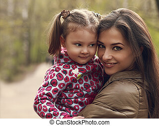 Beautiful happy mother and kid girl cuddling outdoors. Closeup portrait