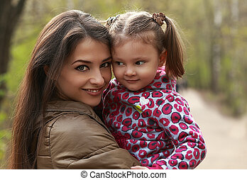 Beautiful mother and kid girl cuddling on green summer background. Closeup