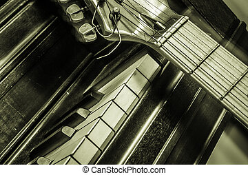 Piano with Guitar - A Guitar is propped up against an old...