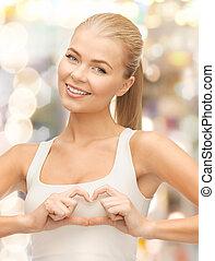 smiling woman showing heart shape gesture - love, happiness...