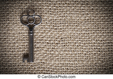 Skeleton Key - An old metal skeleton key sitting on a piece...