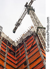 Under Construction - Big City - A large crane works on a...