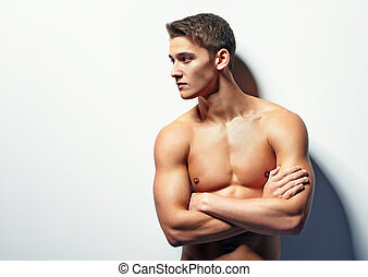 Portrait of muscular young man looking away with naked torso...
