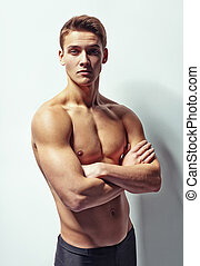 Portrait of a young muscular man with naked torso standing...