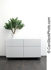 white chest of drawers with flower pot in bright interior