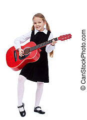 Little girl in black dress holding red guitar, learning to...