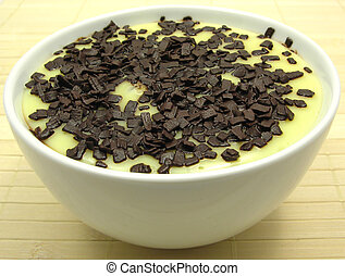 Custard with grated chocolate in a bowl of china ware