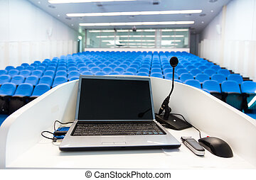 Laptop on the rostrum in conference hall. - Laptop and...