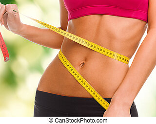 close up of trained belly with measuring tape - sport,...