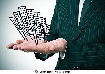 businessman and buildings - a businessman showing a pile of...