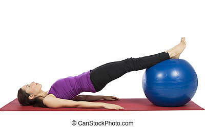 Young fitness woman working her abs with pilates ball -...
