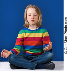 Boy yoga practice - Young boy practicing yoga meditation