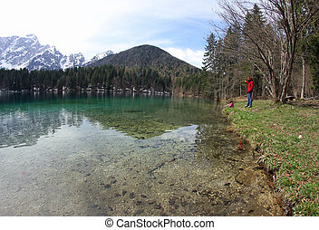 people on the shore of the Lake with the Alps in the...