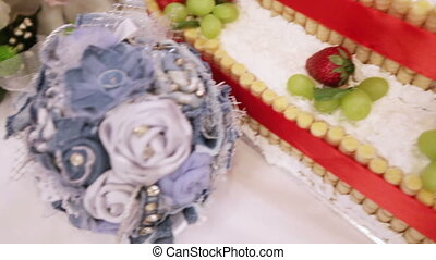 Cake and bridal bouquet - Camera flies over cake and a...