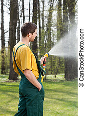 Pouring water with garden hose - Man pouring water with a...