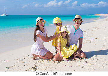 Young family with two kids at tropical white beach