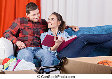 Couple viewing album during moving house - Happy couple...